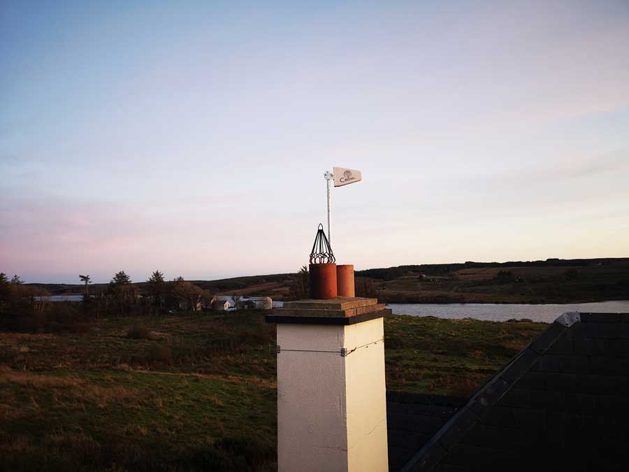 Rooftop antenna in a customer's house in Kilfenora under a bluish sunset sky.